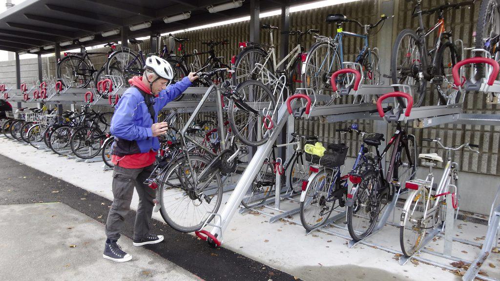 Ein Mann stellt sein Fahrrad auf einen der neuen Fahrradabstellplätze