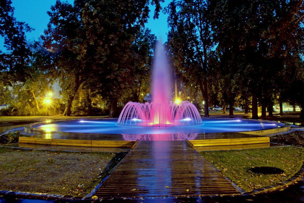 blau und rosa beleuchteter Springbrunnen. Vorderbei ein barrierefreier Steg